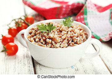 Buckwheat in bowl on white wooden background