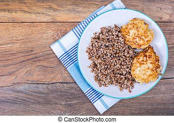 Buckwheat porridge with cutlets on white plate