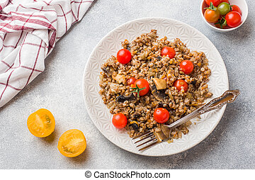 Buckwheat porridge with mushrooms and cherry tomatoes on a plate.