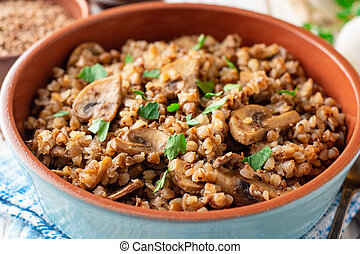 Buckwheat porridge with mushrooms in a bowl on white wooden background