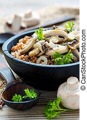 Buckwheat porridge with mushrooms in a wooden bowl.