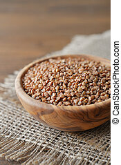 Buckwheat - Raw buckwheat seeds in bowl on wooden background