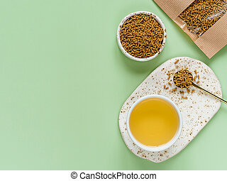 Cup of buckwheat tea on light green background. Top view of healthy soba tea and groats of tartary buckwheat seeds on green background. Flat lay. Copy space
