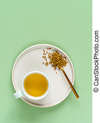 cup of buckwheat tea on light green background. Top view of healthy soba tea and groats in spoon on green paper background. Flat lay. Copy space. Vertical