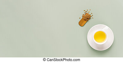 cup of buckwheat tea or kuqiaocha on light green background. Top view of healthy soba tea and groats in spoon on green paper background. Flat lay. Copy space. Long horizontal banner