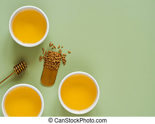 cups of buckwheat tea on light green background. Top view of healthy soba tea and groats of tartary buckwheat seeds on green paper background. Flat lay. Copy space