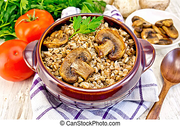 Buckwheat with champignons in clay bowl on napkin - Boiled...