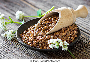 Buckwheat with flower on wooden background