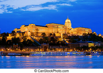 Buda Castle by the Danube river, illuminated at dusk in Budapest, Hungary.