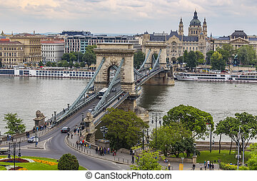 Budapest, Hungary - Szechenyi chain bridge, St. Stephen's Basilica, Danube embankments and pleasure boats at the pier