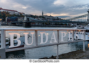 Budapest sign on the banks of the river Danube, with the famous chain link bridge in the background