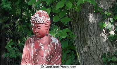 buddah garden ornament under a tree