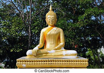 Statue of Buddha meditating in green garden