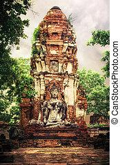 Buddha at Wat Mahathat ruins under sunset sky. Ayutthaya, Thaila