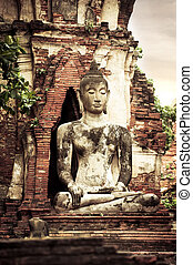 Buddha at Wat Mahathat ruins under sunset sky. Ayutthaya, Thaila