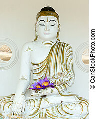 Buddha image statue with fresh flowers in hands