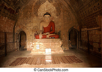Buddha in red robe in buddhist temple in Bagan, Myanmar