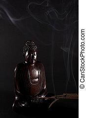 Buddha on black background - Wooden Buddha meditating on the...