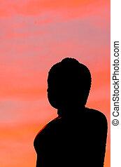 Buddha silhouette on sunset sky