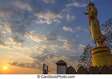 Buddha stand with  sunset