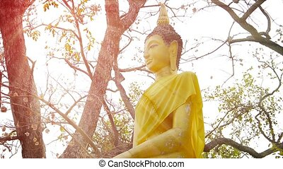 Video 1920X1080 - Gold-Painted Buddha Statue, wearing a yellow sash at Ayutthaya Historical Park in Thailand. A light breeze gently stirs the sash.