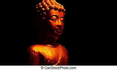 Buddha golden statue is illuminated in firelight