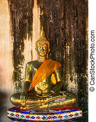 buddha statue on a old brick wall in Thailand