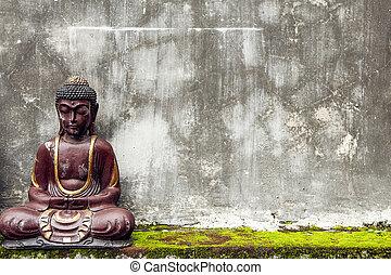 Buddha statue, sitting near old wall
