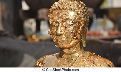 buddha statue with gold leaves - small square of gold leaves...