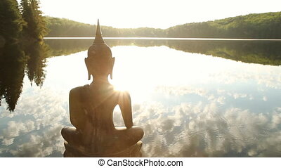 Sculpture of a Buddha looking out over a freshwater lake. Sun reflected in the lake and birds singing. Ontario, Canada.