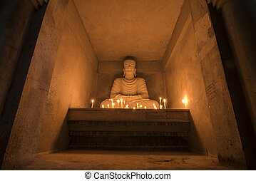 Buddha with bright candles in a brick wall.