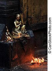 Buddha with candles in the Swayambhunath Stupa, Kathmandu, Buddh