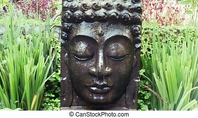 Buddha with falling water in the tropical garden in Ubud,...