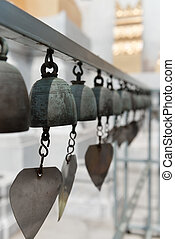 Buddhist bells with wishes in a temple - Many dark metal...
