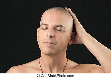 Buddhist Feels Shaved Head - Close-up of a buddhist man...