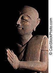 Buddhist monk in serene prayer pose.