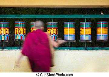 Buddhist monk passing and rotating prayer wheels on kora around Tsuglagkhang complex in McLeod Ganj, Himachal Pradesh, India