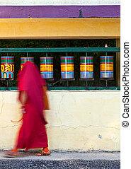 Buddhist monk rotating prayer wheels in McLeod Ganj -...