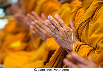 Buddhist monks chanting focus on one hand