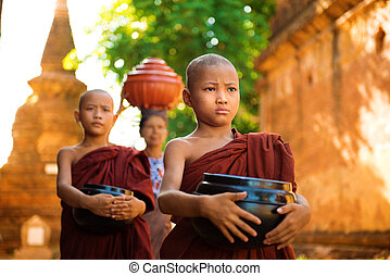 Young Buddhist monks walking morning alms in Old Bagan, Myanmar