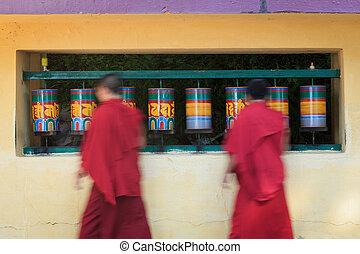 Buddhist monks passing and rotating prayer wheels on kora around Tsuglagkhang complex in McLeod Ganj, Himachal Pradesh, India