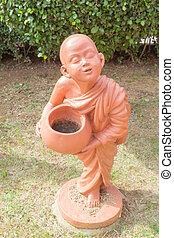 Buddhist novice holding alms bowl clay doll at Thai Buddhist temple
