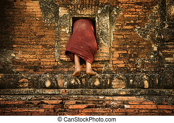 Buddhist novice monk climbing into monastery