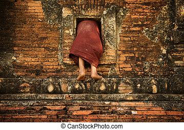 Buddhist novice monk climbing into monastery