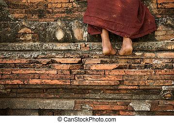 Buddhist novice monk climbing temple