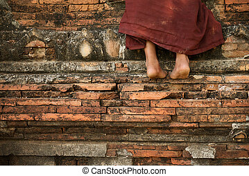 Buddhist novice monk climbing temple