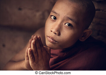 Buddhist novice monk praying in monastery