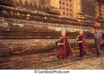 Buddhist novice monks walking alms in Bagan