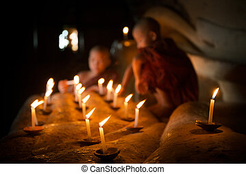 Buddhist novices with candle light inside temple - Little...