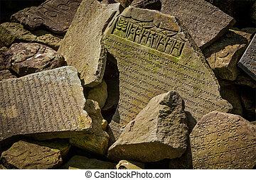 Buddhist prayer mantras on stones in Tibetan Buddhism temple